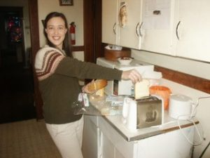 woman smiling putting bread into a toaster