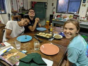 three people smiling, sitting at a dinner table